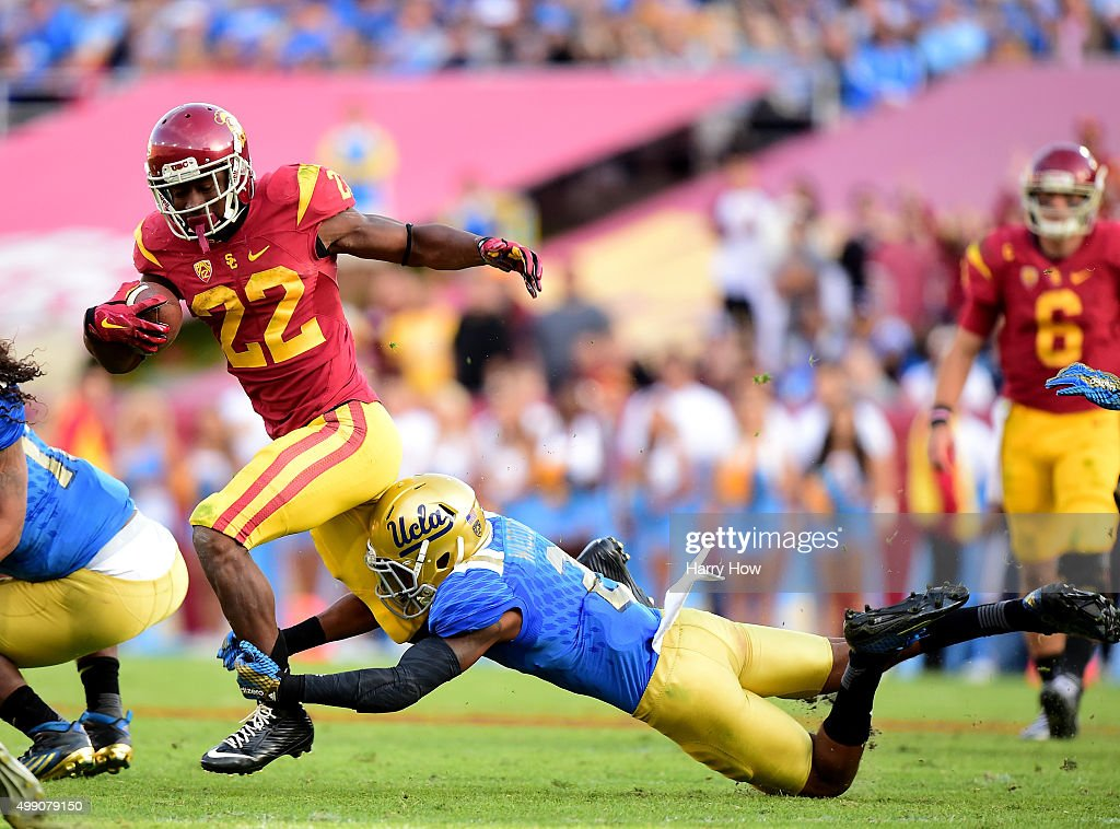 Justin Davis #22 of the USC Trojans is tackled by Jaleel Wadood #2 of the UCLA Bruins during a 40-21 Trojan win at Los Angeles Memorial Coliseum on November 28, 2015 in Los Angeles, California.