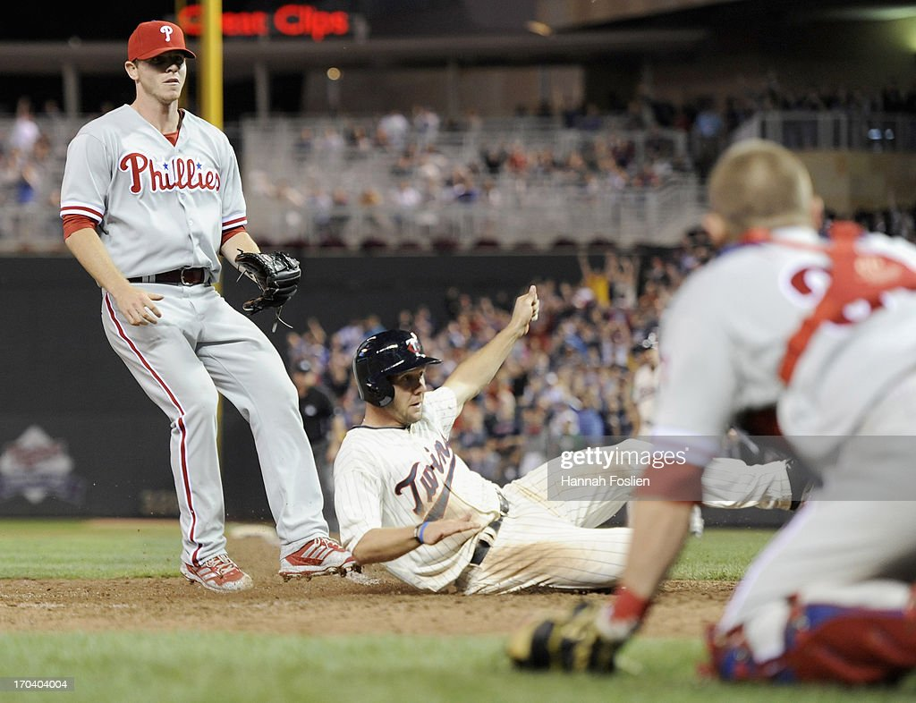 Justin De Fratus #79 and Steve Lerud #39 of the Philadelphia Phillies look on as <a gi-track='captionPersonalityLinkClicked' href=/galleries/search?phrase=Clete+Thomas&family=editorial&specificpeople=4952485 ng-click='$event.stopPropagation()'>Clete Thomas</a> #11 of the Minnesota Twins slides safely into home plate on a wild pitch during the eighth inning of the game on June 12, 2013 at Target Field in Minneapolis, Minnesota. The Twins defeated the Phillies 4-3.