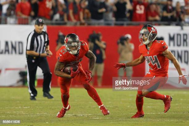 Justin Evans of the Bucs intercepts a pass from Tom Brady in his first career start as Brent Grimes looks on during the NFL Regular game between the...