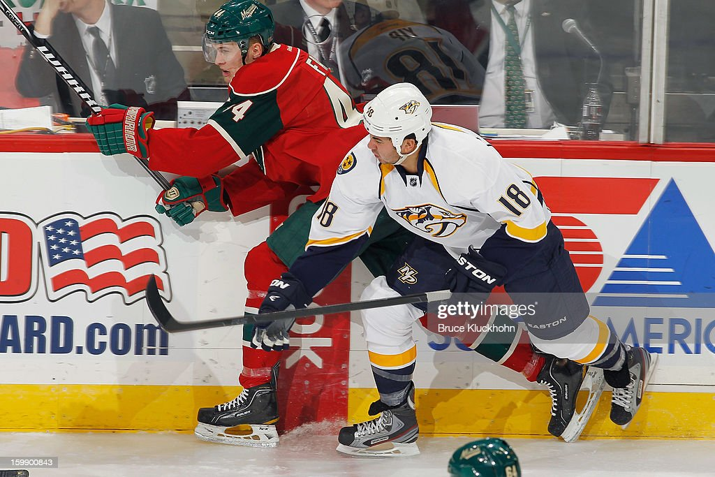 Justin Falk #44 of the Minnesota Wild and Brandon Yip #18 of the Nashville Predators skate to the puck during the game on January 22, 2013 at the Xcel Energy Center in Saint Paul, Minnesota.