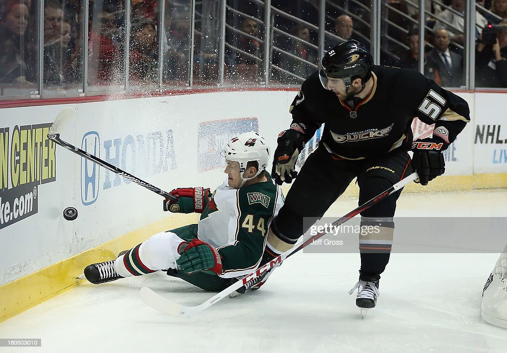 Justin Falk #44 of the Minnesota Wild is checked into the boards by Kyle Palmieri #51 of the Anaheim Ducks while pursuing the puck in the at Honda Center on February 1, 2013 in Anaheim, California.