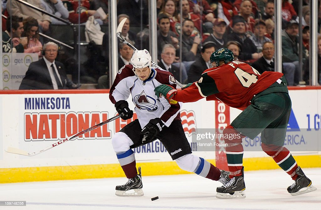 Justin Falk #44 of the Minnesota Wild pushes John Mitchell #7 of the Colorado Avalanche during the third period of the season opener on January 19, 2013 at Xcel Energy Center in St. Paul, Minnesota. The Wild defeated the Avalanche 4-2.