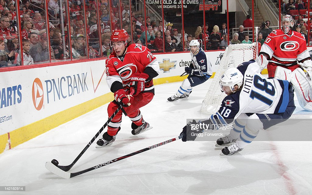 Justin Faulk #28 of the Carolina Hurricanes and <a gi-track='captionPersonalityLinkClicked' href=/galleries/search?phrase=Bryan+Little&family=editorial&specificpeople=540533 ng-click='$event.stopPropagation()'>Bryan Little</a> #18 of the Winnipeg Jets battle for the puck behind the net during an NHL game on March 30, 2012 at PNC Arena in Raleigh, North Carolina.