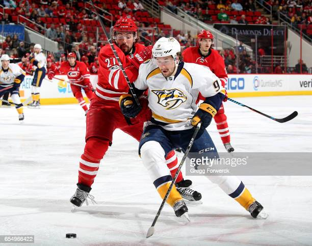 Justin Faulk of the Carolina Hurricanes and Filip Forsberg of the Nashville Predators battle to control a loose puck during an NHL game on March 18...