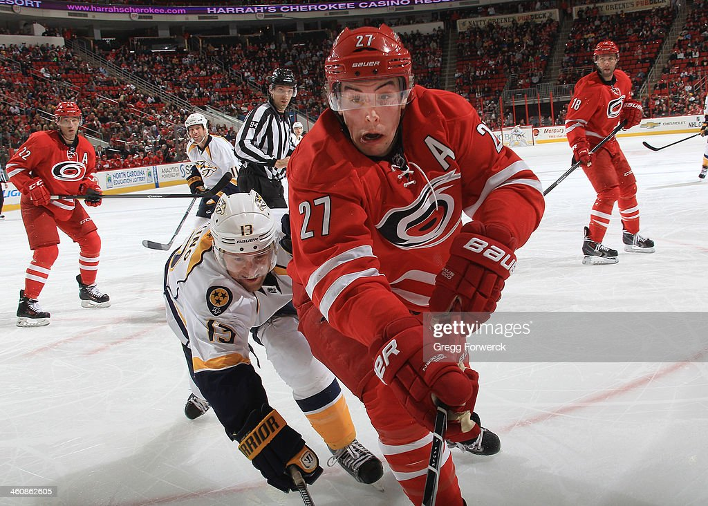 Justin Faulk #27 of the Carolina Hurricanes and <a gi-track='captionPersonalityLinkClicked' href=/galleries/search?phrase=Nick+Spaling&family=editorial&specificpeople=4112920 ng-click='$event.stopPropagation()'>Nick Spaling</a> #13 of the Nashville Predators skate into the corner while battling for the puck during their NHL game at PNC Arena on January 5, 2014 in Raleigh, North Carolina.