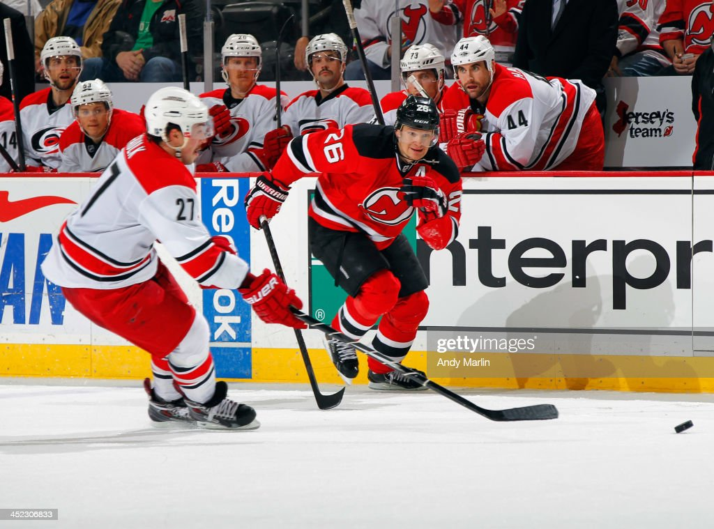 Justin Faulk #27 of the Carolina Hurricanes and <a gi-track='captionPersonalityLinkClicked' href=/galleries/search?phrase=Patrik+Elias&family=editorial&specificpeople=201827 ng-click='$event.stopPropagation()'>Patrik Elias</a> #26 of the New Jersey Devils pursue a loose puck during the game at the Prudential Center on November 27, 2013 in Newark, New Jersey.
