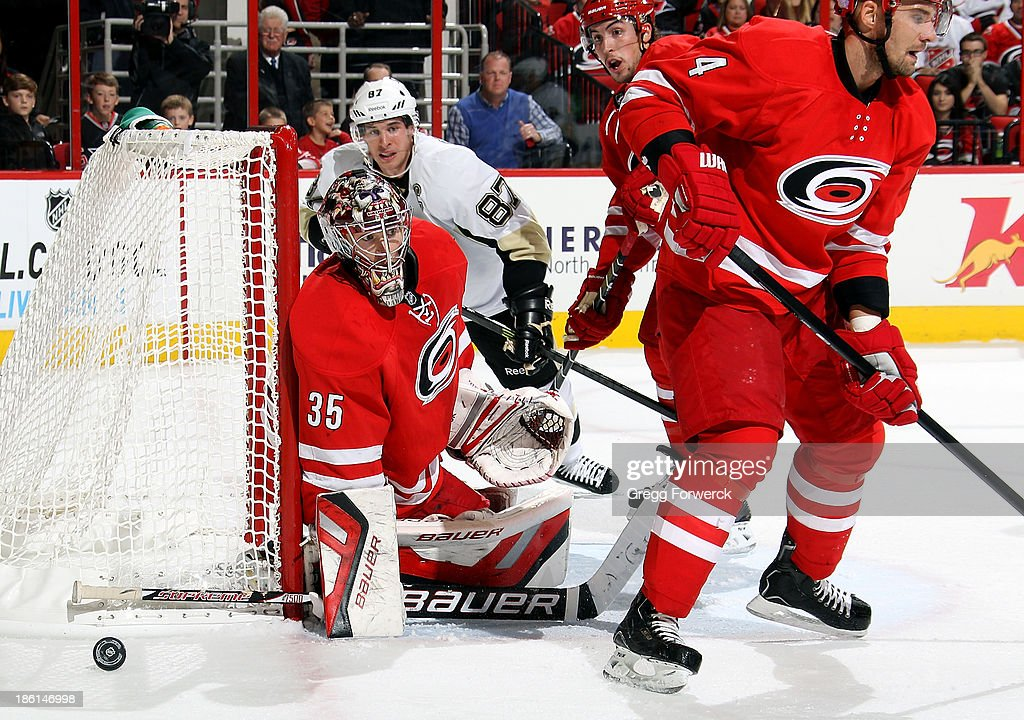 Justin Faulk #27 of the Carolina Hurricanes and Sidney Crosby #87 of the Pittsburgh Penguins watch a shot go wide of Andrej Sekera #4 and Justin Peters #35 during their NHL game at PNC Arena on October 28, 2013 in Raleigh, North Carolina.