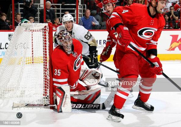 Justin Faulk of the Carolina Hurricanes and Sidney Crosby of the Pittsburgh Penguins watch a shot go wide of Andrej Sekera and Justin Peters during...