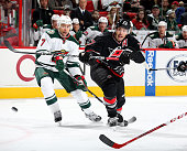 Justin Faulk of the Carolina Hurricanes backhands the puck on net past the defense of Chris Porter of the Minnesota Wild during a NHL game at PNC...