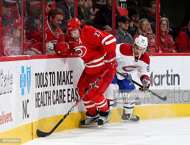 Justin Faulk of the Carolina Hurricanes battles along the boards with Charles Hudon of the Montreal Canadiens during an NHL game on November 18 2016...