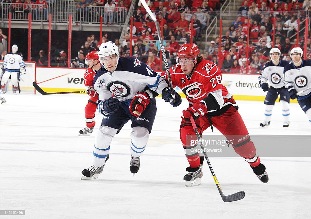 Justin Faulk #28 of the Carolina Hurricanes battles for position against Spencer Machacek #46 of the Winnipeg Jets during an NHL game on March 30, 2012 at PNC Arena in Raleigh, North Carolina.