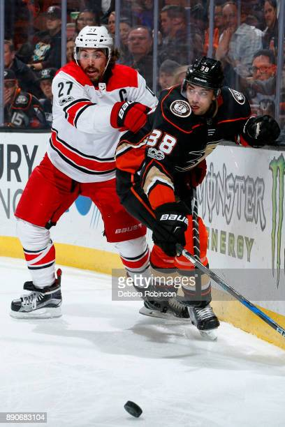 Justin Faulk of the Carolina Hurricanes battles for the puck against Derek Grant of the Anaheim Ducks during the game on December 11 2017 at Honda...