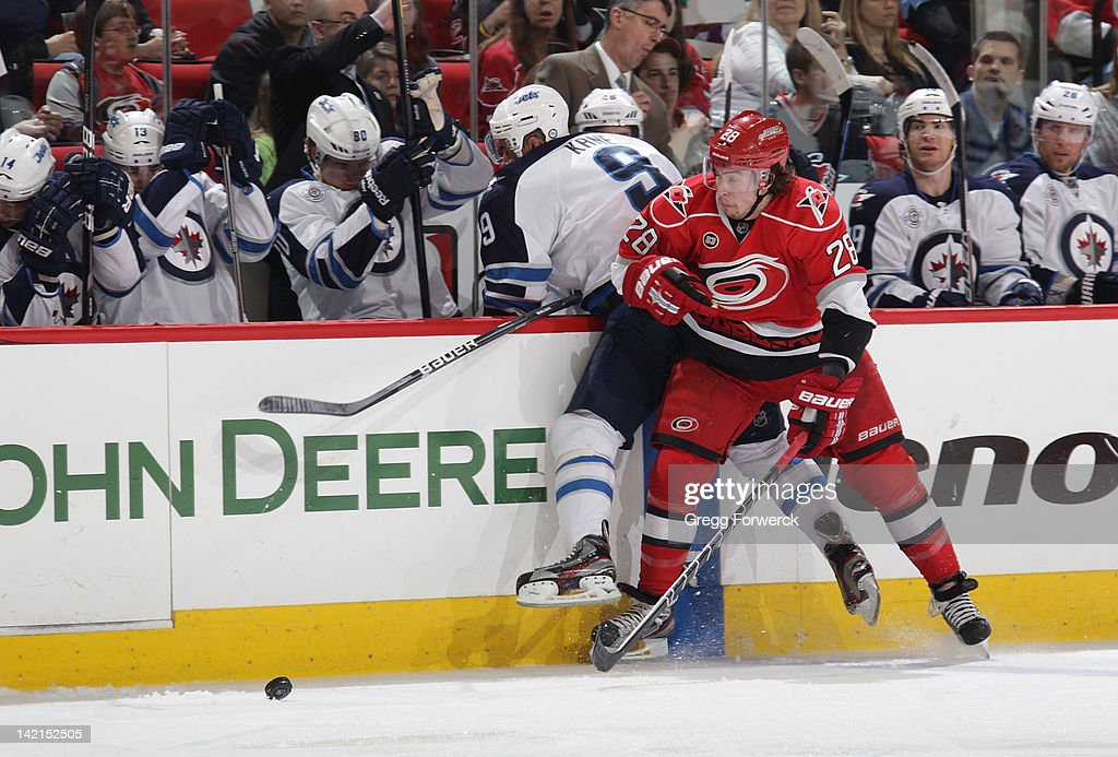 Justin Faulk #28 of the Carolina Hurricanes checks <a gi-track='captionPersonalityLinkClicked' href=/galleries/search?phrase=Evander+Kane&family=editorial&specificpeople=4303789 ng-click='$event.stopPropagation()'>Evander Kane</a> #9 of the Winnipeg Jets int o his own bench during an NHL game on March 30, 2012 at PNC Arena in Raleigh, North Carolina.