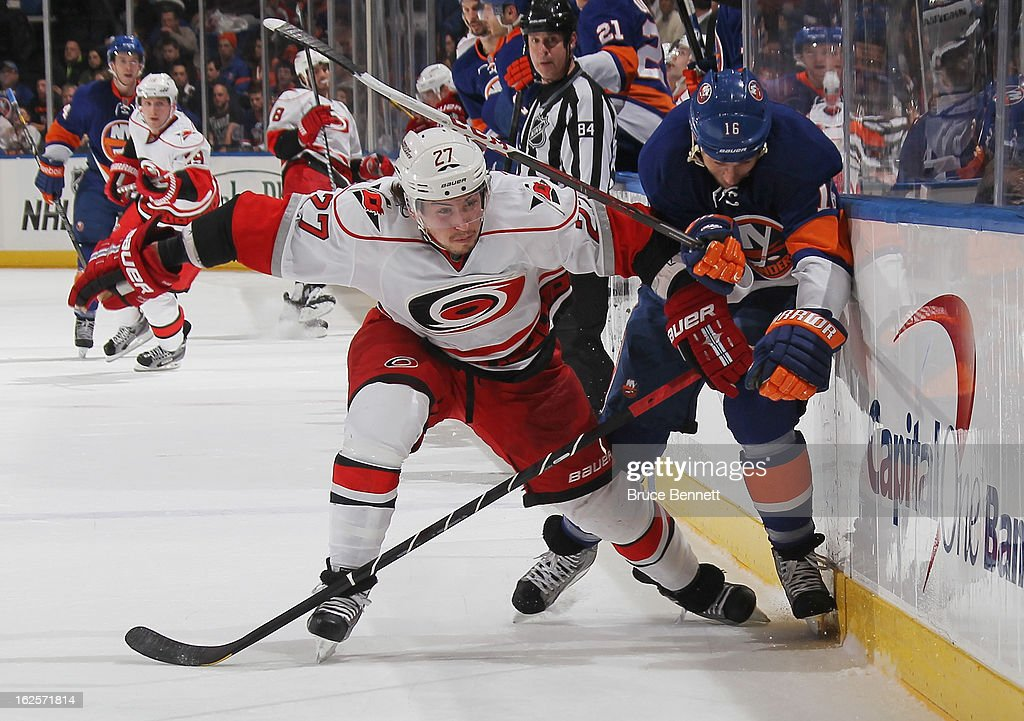Justin Faulk of the Carolina Hurricanes checks Marty Reasoner of the New York Islanders along the boards at the Nassau Veterans Memorial Coliseum on...