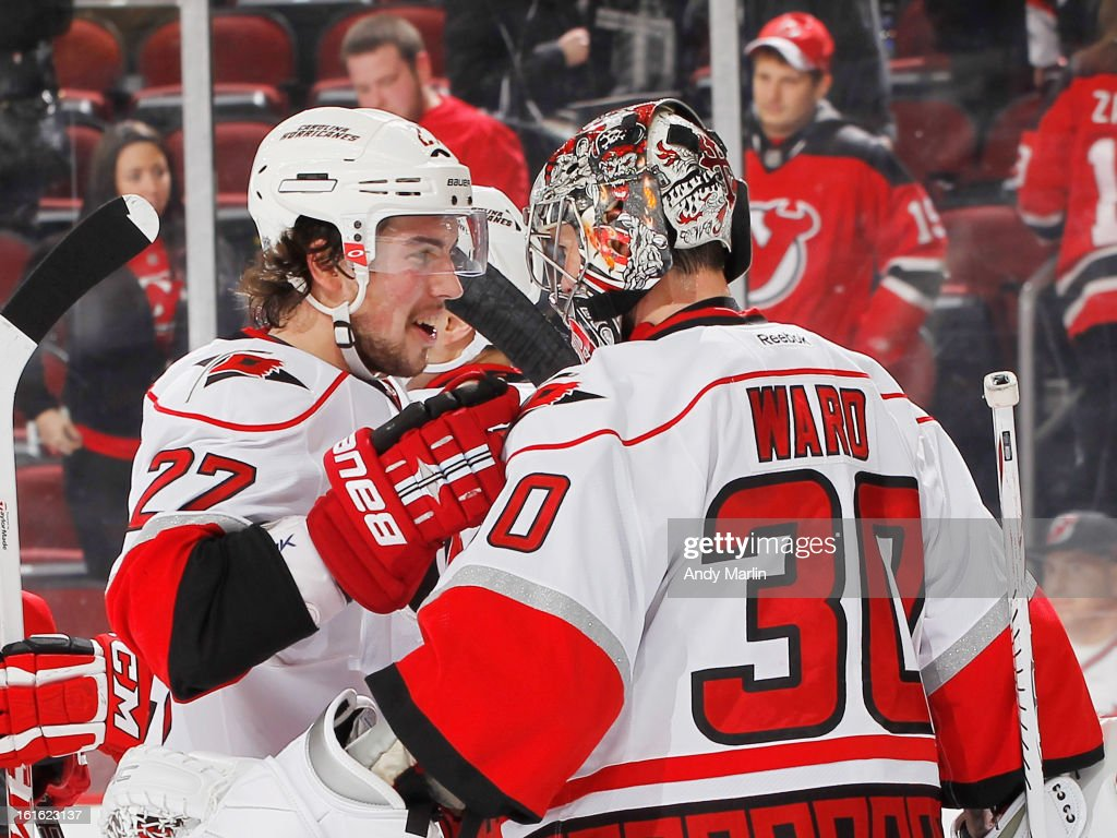Justin Faulk #27 of the Carolina Hurricanes congratulates winning goaltender Cam Ward #30 after the Hurricanes defeated the New Jersey Devils at the Prudential Center on February 12, 2013 in Newark, New Jersey.