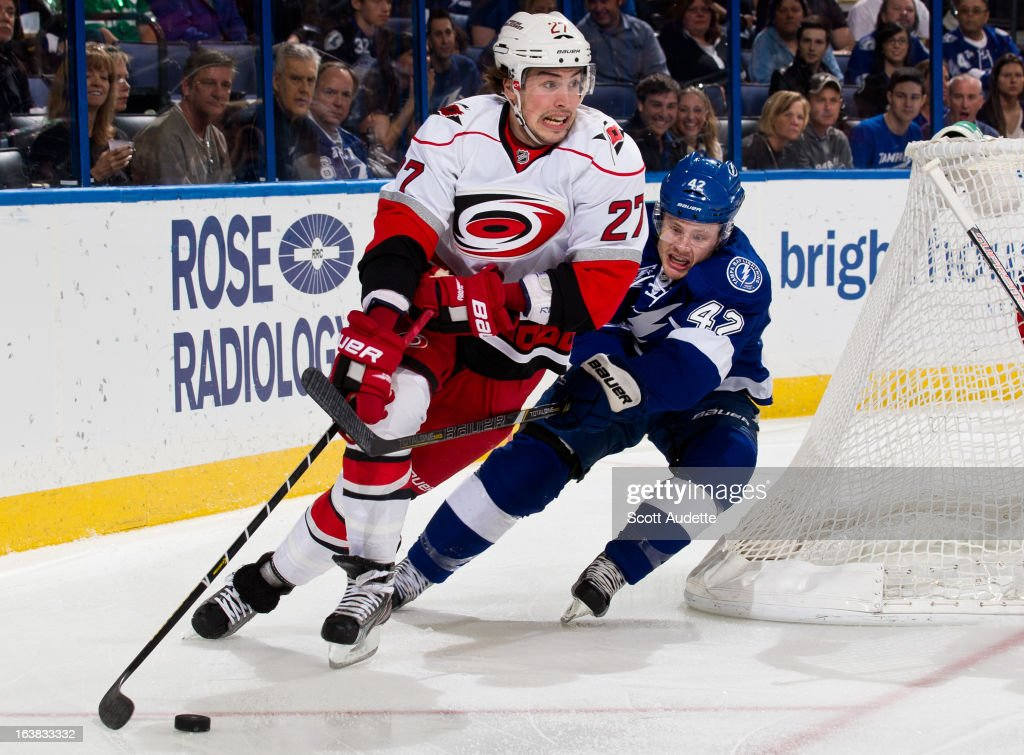 Justin Faulk #27 of the Carolina Hurricanes controls the puck in front of <a gi-track='captionPersonalityLinkClicked' href=/galleries/search?phrase=Dana+Tyrell&family=editorial&specificpeople=2129723 ng-click='$event.stopPropagation()'>Dana Tyrell</a> #42 of the Tampa Bay Lightning during the first period of the game at the Tampa Bay Times Forum on March 16, 2013 in Tampa, Florida.