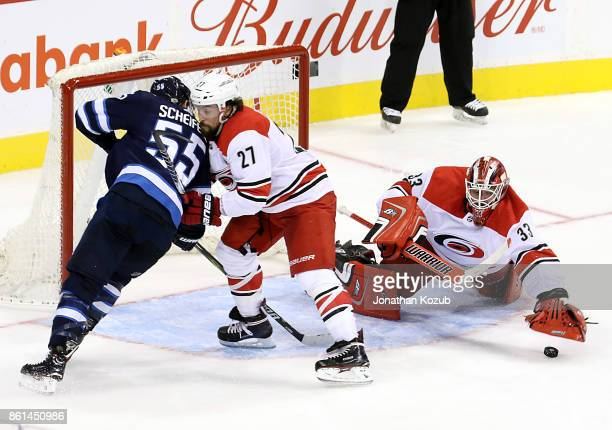 Justin Faulk of the Carolina Hurricanes defends against Mark Scheifele of the Winnipeg Jets as goaltender Scott Darling covers up the loose puck...
