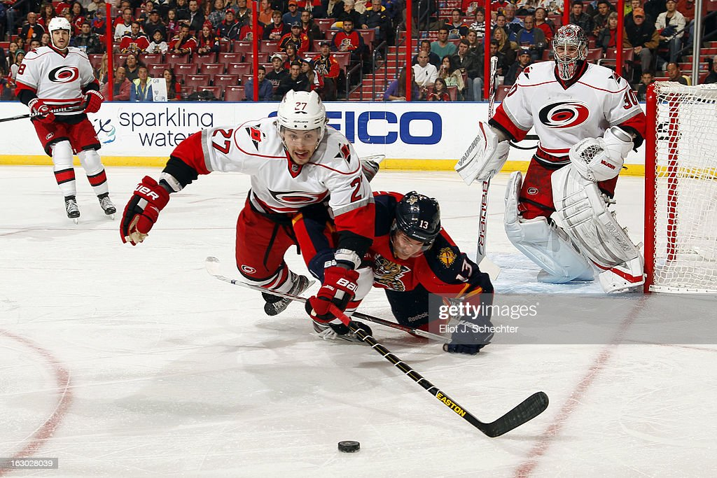 Justin Faulk #27 of the Carolina Hurricanes dives for the puck against Mike Santorelli #13 of the Florida Panthers at the BB&T Center on March 3, 2013 in Sunrise, Florida.
