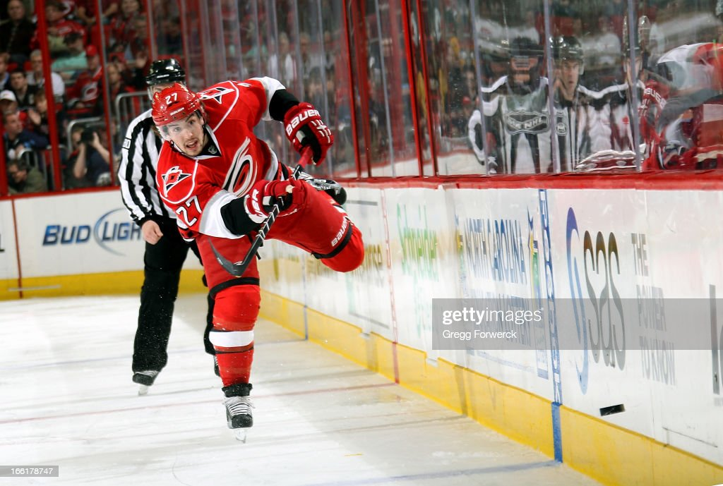 Justin Faulk #27 of the Carolina Hurricanes dumps the puck during an NHL game against the Pittsburgh Penguins during their NHL game at PNC Arena on April 9, 2013 in Raleigh, North Carolina.