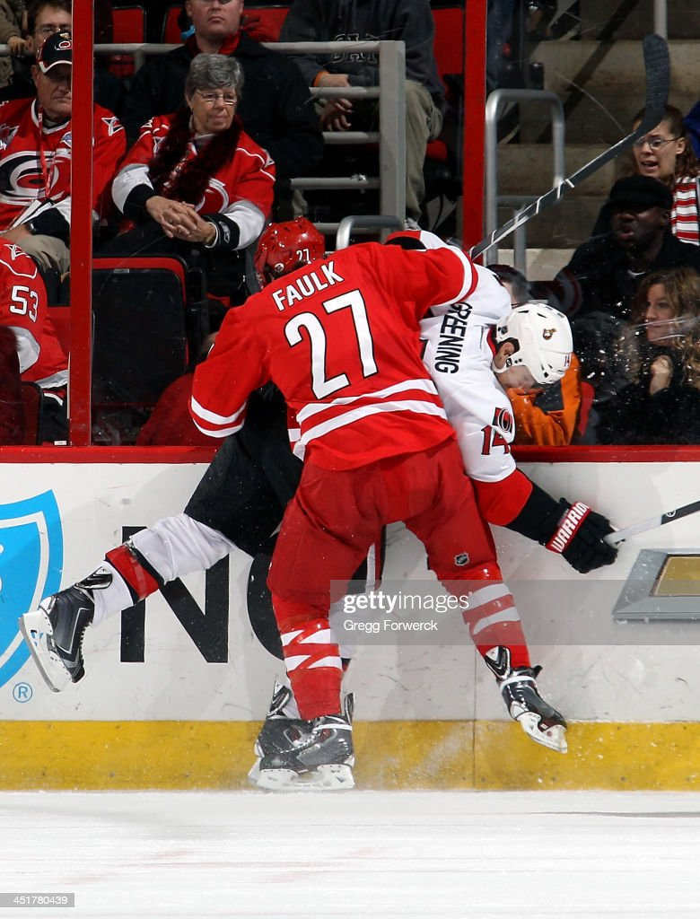 Justin Faulk #27 of the Carolina Hurricanes finishes a check on <a gi-track='captionPersonalityLinkClicked' href=/galleries/search?phrase=Colin+Greening&family=editorial&specificpeople=7183741 ng-click='$event.stopPropagation()'>Colin Greening</a> #14 of the Ottawa Senators during their NHL game at PNC Arena on November 24, 2013 in Raleigh, North Carolina.