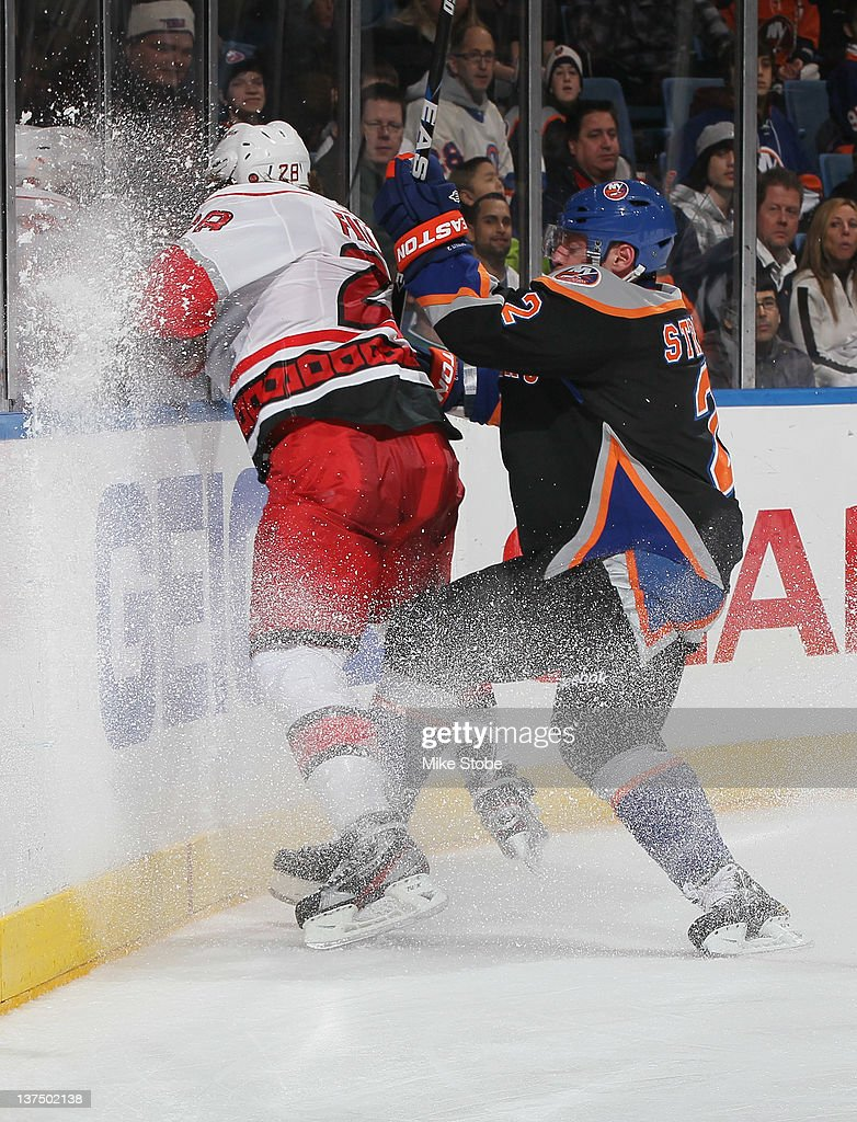 Justin Faulk of the Carolina Hurricanes is checked into the boards by Mark Streit of the New York Islanders at Nassau Veterans Memorial Coliseum on...