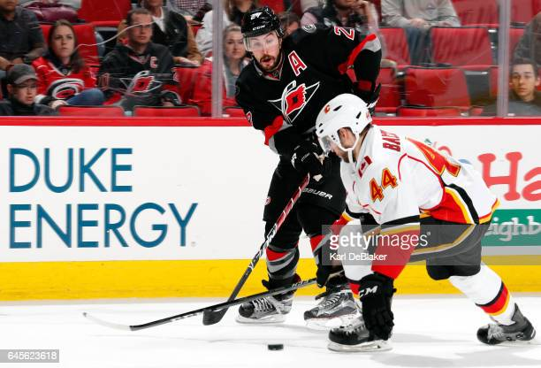 Justin Faulk of the Carolina Hurricanes passes the puck under the stick of Matt Bartkowski of the Calgary Flames during an NHL game on February 26...