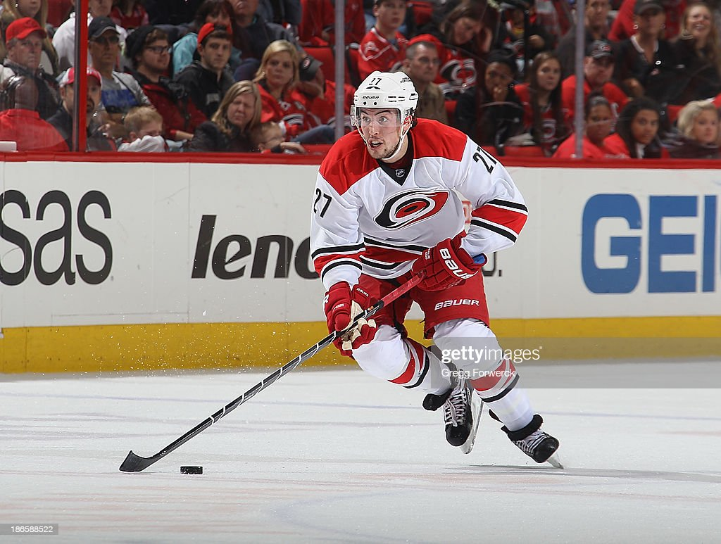 Justin Faulk #27 of the Carolina Hurricanes skates with the puck during their NHL game against the Tampa Bay Lightning at PNC Arena on November 1, 2013 in Raleigh, North Carolina.