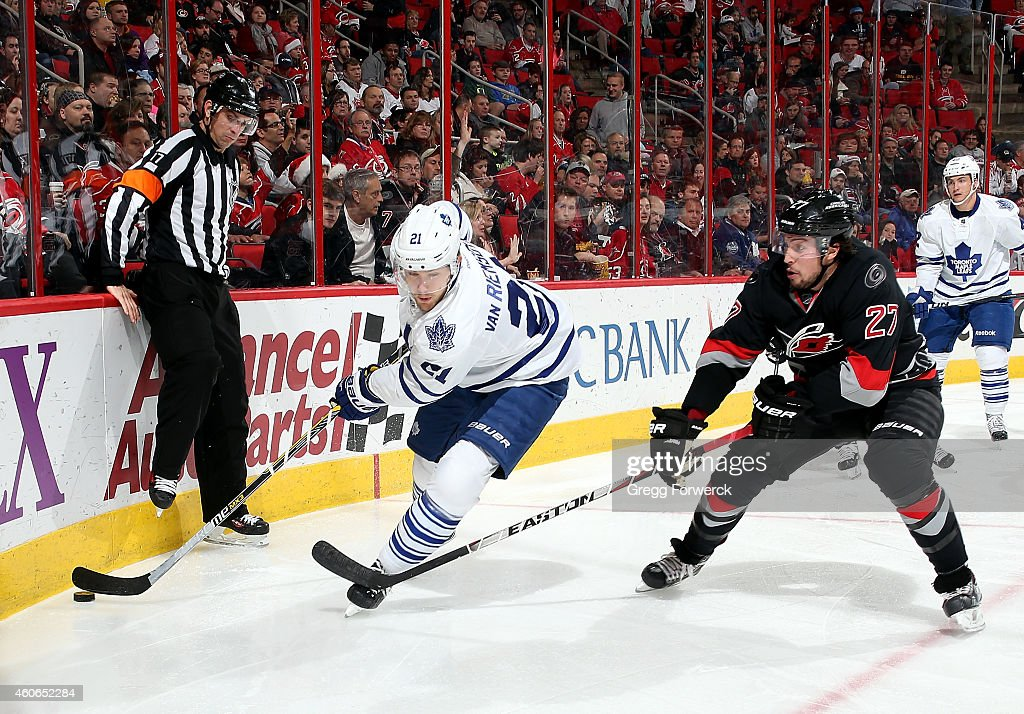 Justin Faulk #27 of the Carolina Hurricanes stick checks James van Riemsdyk #21 of the Toronto Maple Leafs as he moves the puck around the boards during their NHL game at PNC Arena on December 18, 2014 in Raleigh, North Carolina.