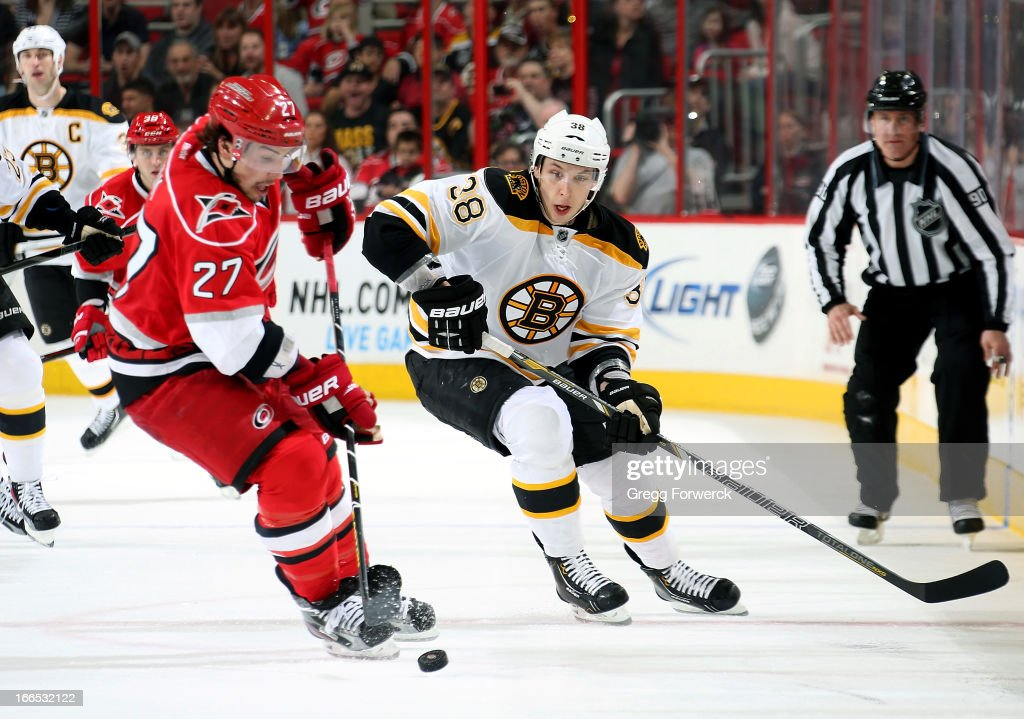 Justin Faulk #27 of the Carolina Hurricanes takes control of the puck ahead of Jordan Caron #38 of the Boston Bruins during their NHL game at PNC Arena on April 13, 2013 in Raleigh, North Carolina.