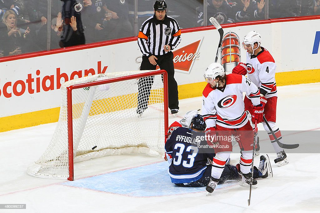 Justin Faulk #27 of the Carolina Hurricanes turns to look at the puck in the net as <a gi-track='captionPersonalityLinkClicked' href=/galleries/search?phrase=Dustin+Byfuglien&family=editorial&specificpeople=672505 ng-click='$event.stopPropagation()'>Dustin Byfuglien</a> #33 of the Winnipeg Jets lays tangled in the crease with goaltender <a gi-track='captionPersonalityLinkClicked' href=/galleries/search?phrase=Cam+Ward&family=editorial&specificpeople=453216 ng-click='$event.stopPropagation()'>Cam Ward</a> #30 during third period action at the MTS Centre on March 22, 2014 in Winnipeg, Manitoba, Canada. The goal was reviewed and disallowed due to Byfuglien in the crease.