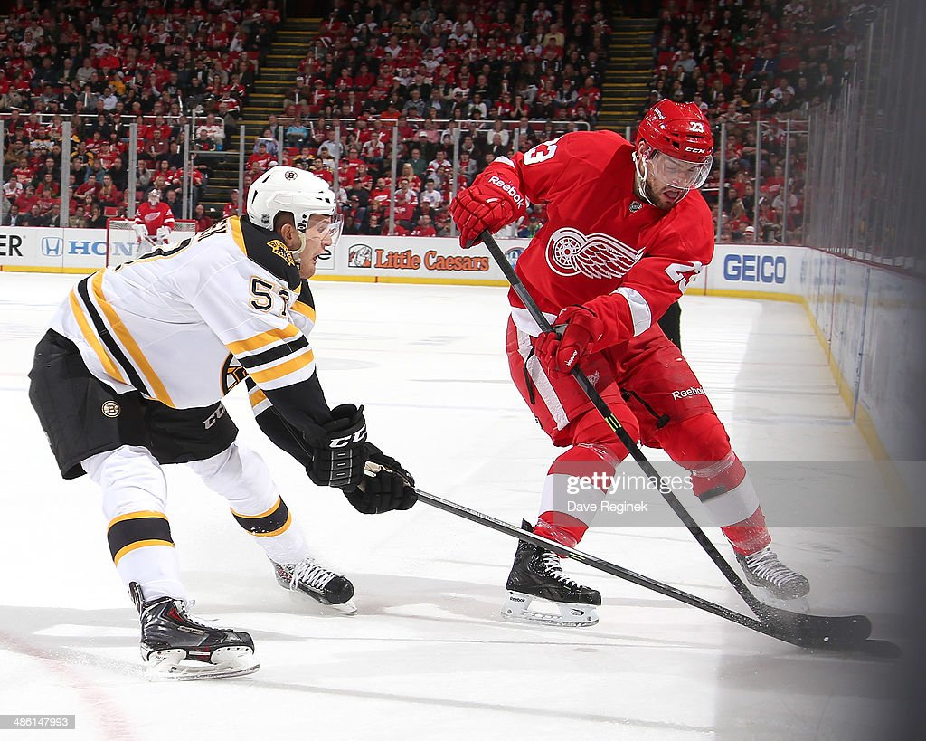 Justin Florek #57 of the Boston Bruins and Brian Lashoff #23 of the Detroit Red Wings battle for the puck along the boards during Game Three of the First Round of the 2014 Stanley Cup Playoffs on April 22, 2014 at Joe Louis Arena in Detroit, Michigan.