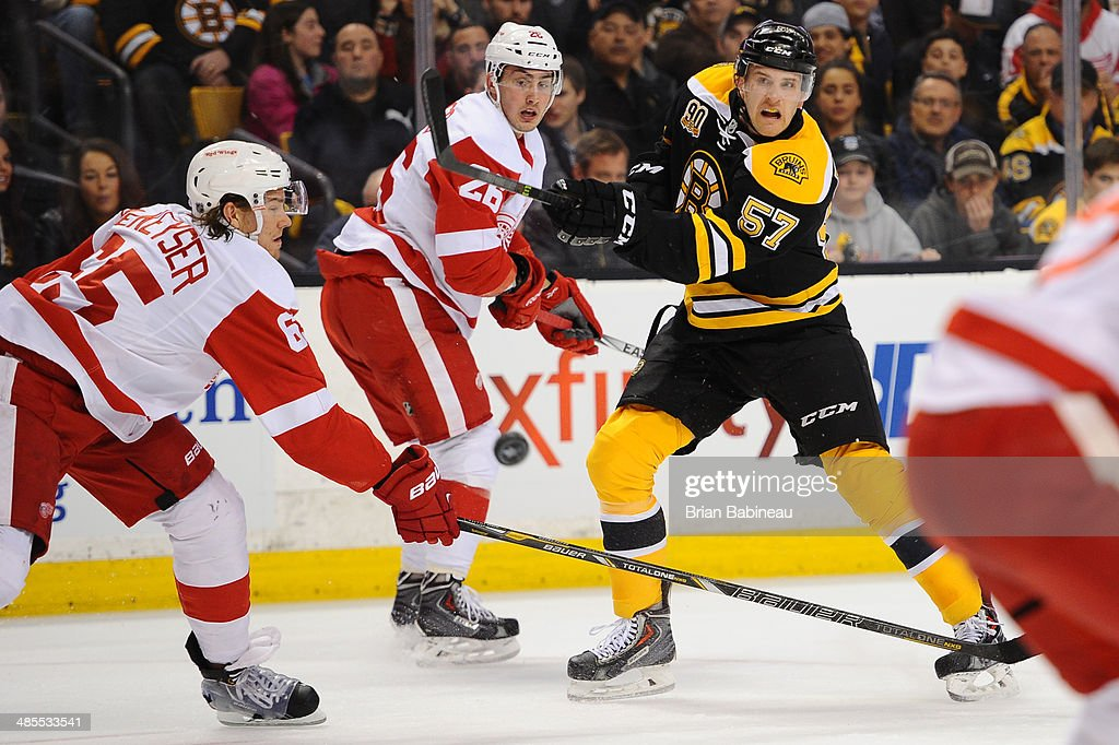 Justin Florek #57 of the Boston Bruins shoots the puck against Danny DeKeyser #65 and Tomas Jurco #26 of the Detroit Red Wings in Game One of the First Round of the 2014 Stanley Cup Playoffs at TD Garden on April 18, 2014 in Boston, Massachusetts.