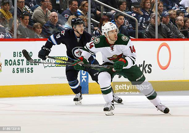 Justin Fontaine of the Minnesota Wild and Nic Petan of the Winnipeg Jets follow the play down the ice during first period action at the MTS Centre on...