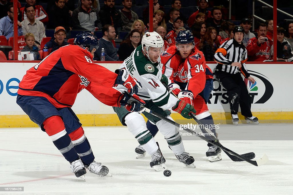 <a gi-track='captionPersonalityLinkClicked' href=/galleries/search?phrase=Justin+Fontaine&family=editorial&specificpeople=8312194 ng-click='$event.stopPropagation()'>Justin Fontaine</a> #14 of the Minnesota Wild battles for the puck against <a gi-track='captionPersonalityLinkClicked' href=/galleries/search?phrase=Alexander+Urbom&family=editorial&specificpeople=6254340 ng-click='$event.stopPropagation()'>Alexander Urbom</a> #34 and Steve Oleksy #61 of the Washington Capitals in the third period during an NHL game at Verizon Center on November 7, 2013 in Washington, DC.