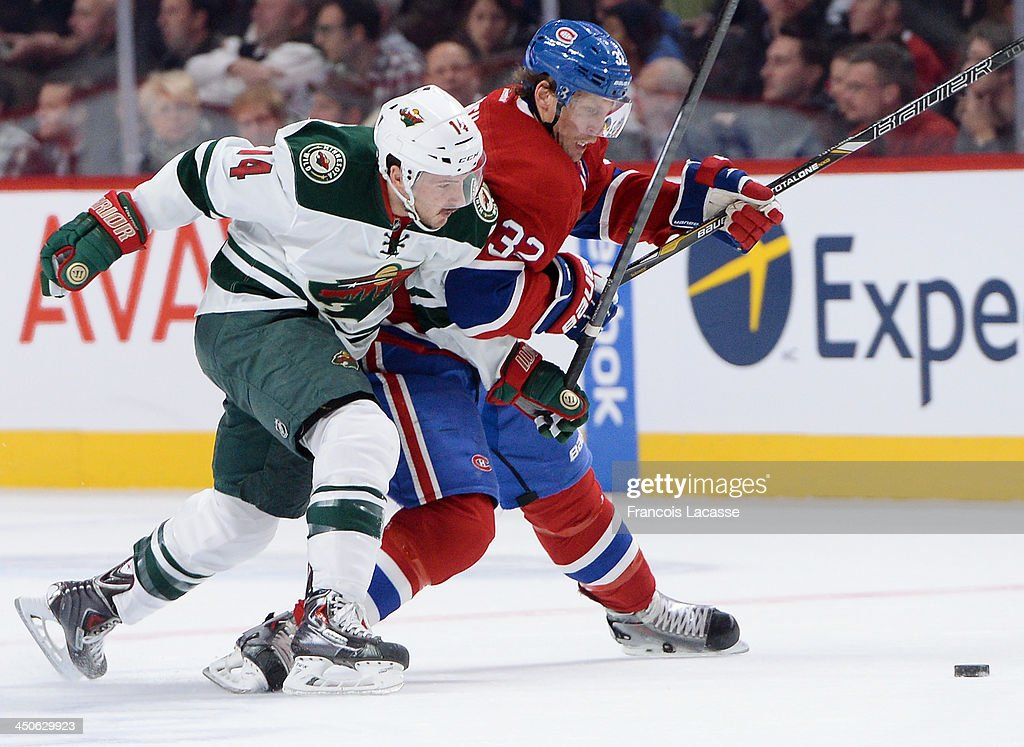 Justin Fontaine #14 of the Minnesota Wild challenges Travis Moen #32 of the Montreal Canadiens during the NHL game on November 19, 2013 at the Bell Centre in Montreal, Quebec, Canada.