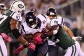 Justin Forsett of the Houston Texans runs the ball in the first quarter against Calvin Pace and David Harris of the New York Jets at MetLife Stadium...