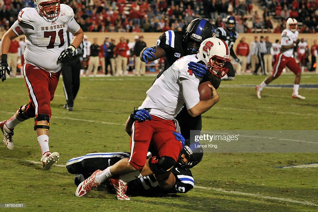 Justin Foxx #92 and Carlos Wray #98 of the Duke Blue Devils tackle <a gi-track='captionPersonalityLinkClicked' href=/galleries/search?phrase=Pete+Thomas&family=editorial&specificpeople=4598308 ng-click='$event.stopPropagation()'>Pete Thomas</a> #4 of the North Carolina State Wolfpack at Wallace Wade Stadium on November 9, 2013 in Durham, North Carolina. Duke defeated NC State 38-20.