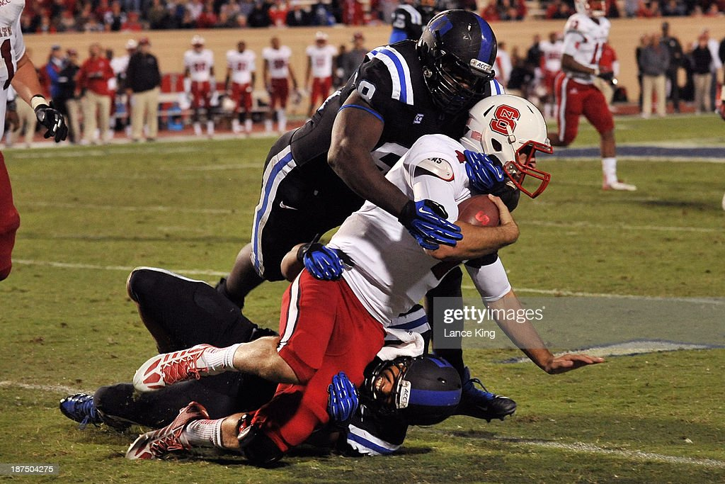 Justin Foxx #92 and Carlos Wray #98 of the Duke Blue Devils tackle Pete Thomas #4 of the North Carolina State Wolfpack at Wallace Wade Stadium on November 9, 2013 in Durham, North Carolina. Duke defeated NC State 38-20.