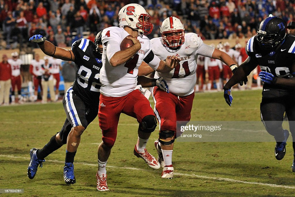 Justin Foxx #92 of the Duke Blue Devils tackles Pete Thomas #4 of the North Carolina State Wolfpack at Wallace Wade Stadium on November 9, 2013 in Durham, North Carolina. Duke defeated NC State 38-20.