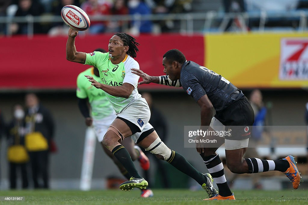 Justin Geduld #9 of South Africa gets a pass away under pressure from Donasio Ratubuli Naturaga #8 of Fiji during the Tokyo Sevens, in the six round of the HSBC Sevens World Series at the Prince Chichibu Memorial Ground on March 23, 2014 in Tokyo, Japan.