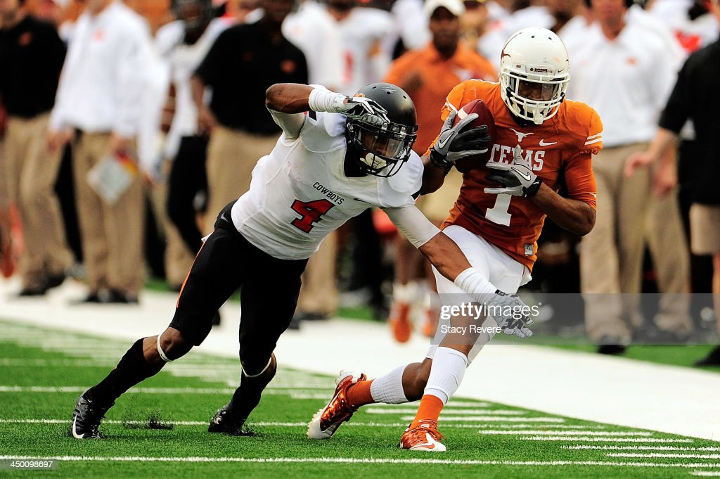 Justin Gilbert #4 of the Oklahoma State Cowboys pursues Mike Davis #1 of the Texas Longhorns during a game at Darrell K Royal-Texas Memorial Stadium on November 16, 2013 in Austin, Texas. Oklahoma State won the game 38-13.