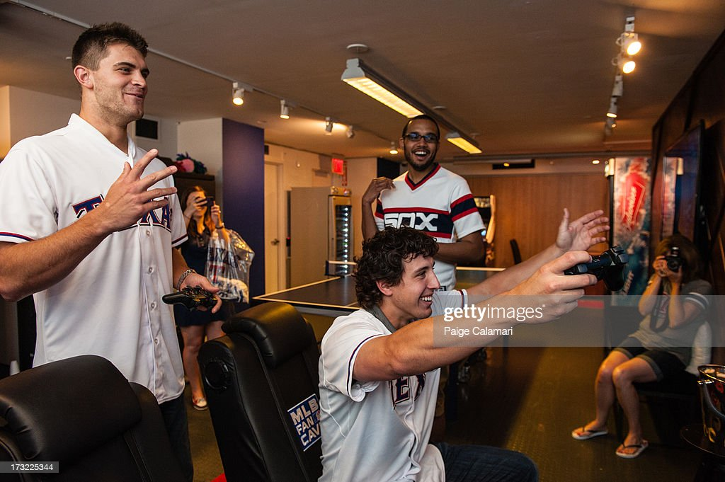 <a gi-track='captionPersonalityLinkClicked' href=/galleries/search?phrase=Justin+Grimm&family=editorial&specificpeople=9480126 ng-click='$event.stopPropagation()'>Justin Grimm</a> and Derek Holland of the Texas Rangers react after playing MLB 13: The Show on Playstation 3 at the MLB Fan Cave on June 25, 2013 at Broadway and 4th Street in New York City.