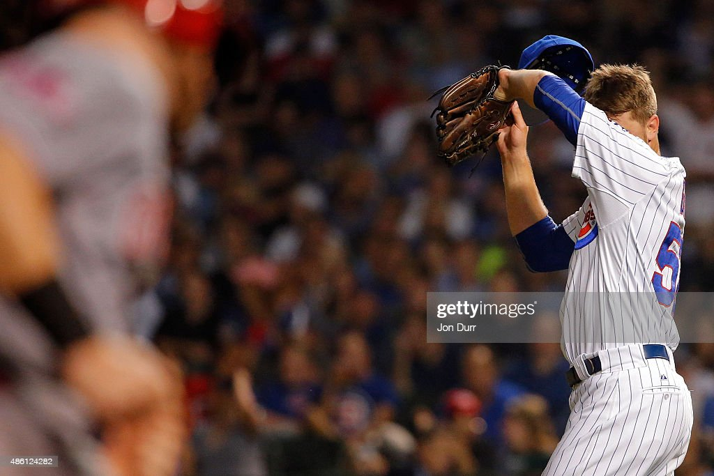 Justin Grimm #52 of the Chicago Cubs reacts after giving up the second two-run home run of the sixth inning to Adam Duvall #23 of the Cincinnati Reds (L) at Wrigley Field on August 31, 2015 in Chicago, Illinois.