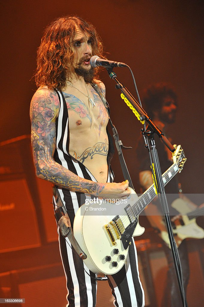 Justin Hawkins and Frankie Poullain of The Darkness perform on stage at Hammersmith Apollo on March 7, 2013 in London, England.
