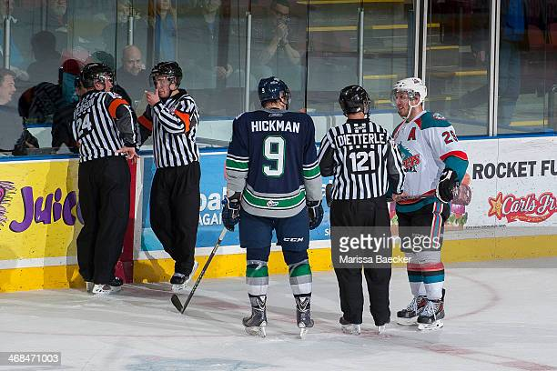 Justin Hickman of the Seattle Thunderbirds and Myles Bell of the Kelowna Rockets await the decision of officials with respect to third period...