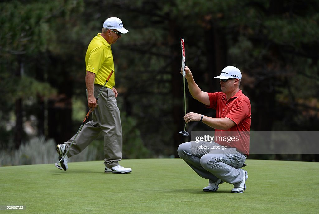 Justin Hicks aims for a putt on the fourth hole as Billy Mayfair walks by during the first round of the Barracuda Championship at the Montreux Golf...