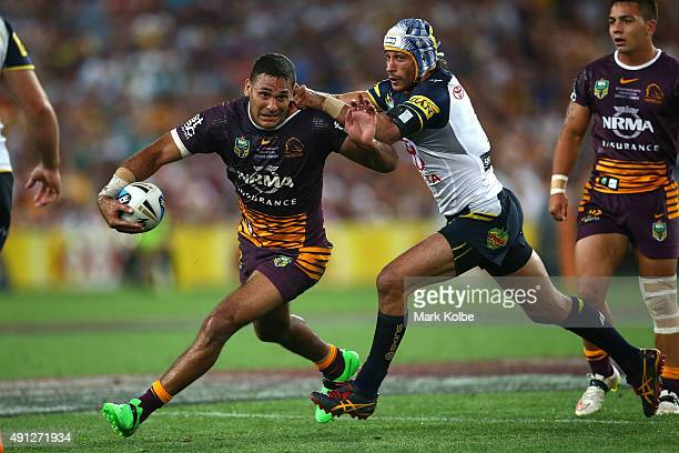 Justin Hodges of the Broncos is tackled by Johnathan Thurston of the Cowboys during the 2015 NRL Grand Final match between the Brisbane Broncos and...