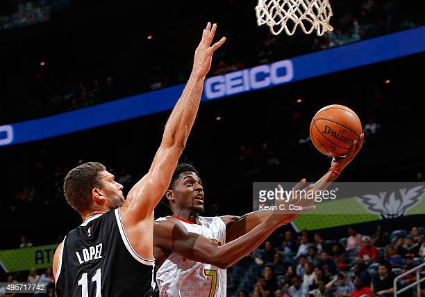 Justin Holiday of the Atlanta Hawks drives the basket against Brook Lopez of the Brooklyn Nets at Philips Arena on November 4 2015 in Atlanta Georgia...
