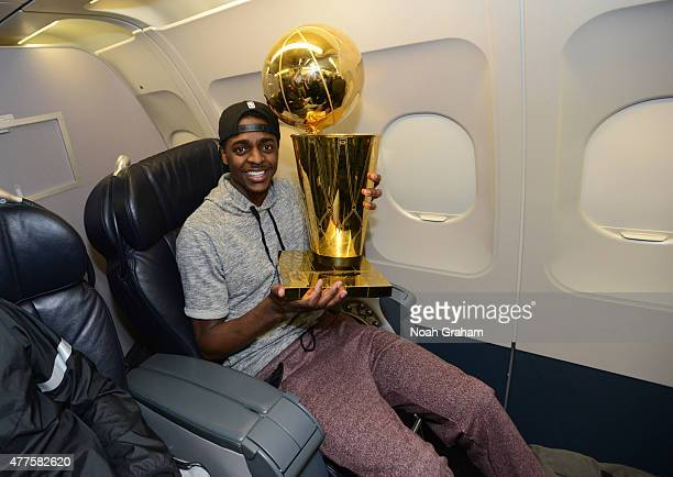 Justin Holiday of the Golden State Warriors holds the NBA trophy on the plane as the team travels home from Cleveland after winning the 2015 NBA...