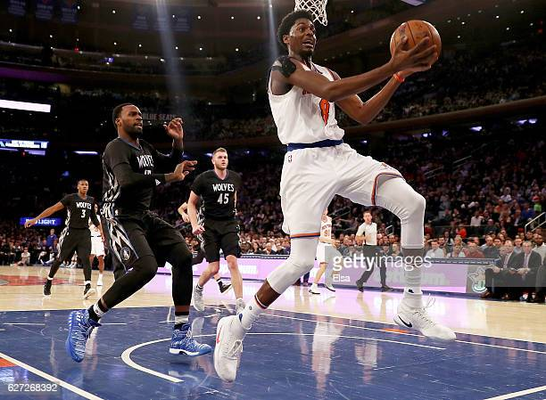 Justin Holiday of the New York Knicks leaps to keep the ball in bounds as Shabazz Muhammad of the Minnesota Timberwolves looks on in the second half...